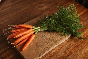 Bunch of carrots on an old cutting board