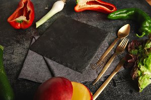 Vegetables around a black slate cheese board