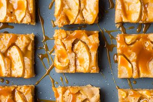Apple blonde brownies with caramel on tray blue background