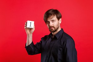 Man holding cube with number one