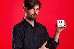 Man holding cube with number two