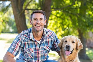 Happy man with his pet dog in park
