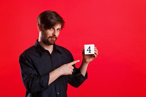 Man holding cube with number four