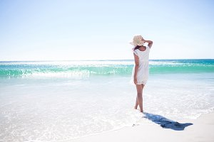 Pretty brunette wearing straw hat and walking in the water