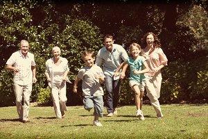 Happy multi generation family running towards camera