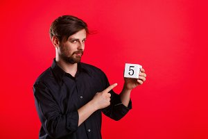 Man holding cube with number five