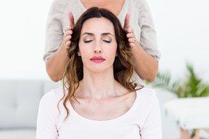 Calm woman receiving reiki treatment