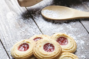 Close-up of biscuits with strawberry jam next to a rolling pin and wooden spoon on wooden table. Horizontal shoot
