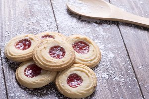 Close-up of biscuits with strawberry jam next to a wooden spoon on wooden table. Horizontal release.