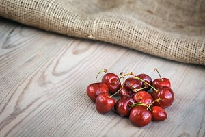 Cherries on wood and sack