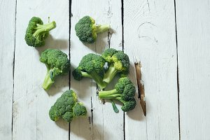 Fresh raw organic broccoli on wooden white background
