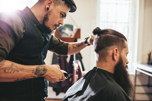 Beard man getting haircut at salon