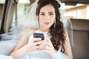 Beautiful bride sitting in car straight with mobile phone hairstyle and bright makeup.