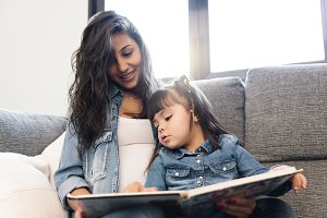Mother reading book to her daughter.