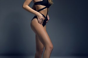 young sexual girl blonde long hair in black swimsuit