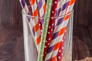 Colorful drinking striped straws in glass on a wooden table with sacking