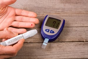 blood glucose meter with a hand on an old wooden background