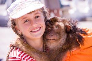 pet monkey hugging a girl on the street