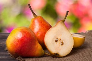 two whole and half of pear on a wooden table with cloth burlap