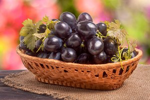 Blue grapes in a wicker basket on wooden table with  blurred background