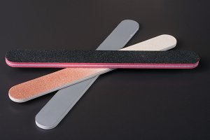 Three nail file with a different abrasive on dark background
