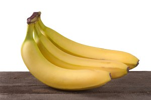 Three bananas on a wooden board isolated  white background