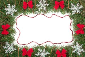 Christmas frame made of fir branches decorated with bows and snowflakes isolated on white background