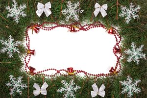 Christmas frame made of fir branches decorated with bows bells and snowflakes isolated on white background