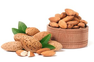 Almonds in a wooden bowl with leaves isolated on white background