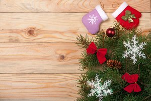 decorated Christmas fir branch on a light wooden background