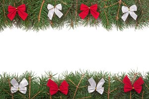 Christmas frame made of fir branches decorated with bows isolated on white background