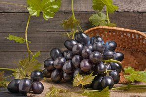 Blue grapes in a wicker basket on wooden table