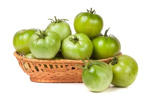 unripe green tomatoes in a wicker basket isolated on white background