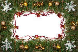 Christmas frame made of fir branches decorated with balls bells and snowflakes isolated on white background