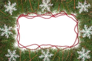 Christmas frame made of fir branches decorated with beads and snowflakes isolated on white background
