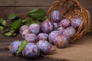 plum in a wicker basket on the wooden background with sackcloth