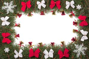 Christmas frame made of fir branches decorated with bows and bells isolated on white background
