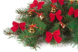 branch of Christmas tree decorated bells and bows isolated on white background
