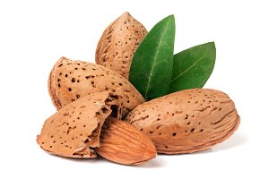 almonds in their skins and peeled with leaf isolated on white background