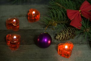 Christmas composition of fir branches decorated bows and balls with burning candles on a wooden background