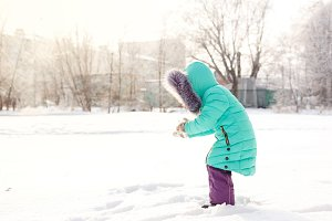Little girl making snowballs