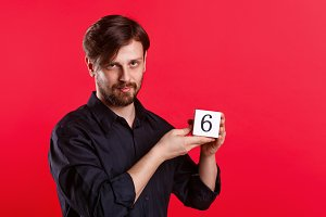 Man holding cube with number six
