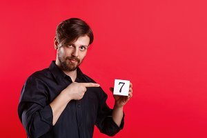 Man holding cube with number seven
