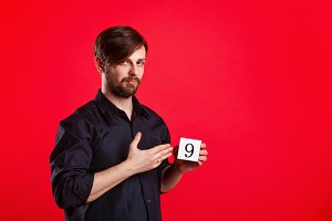 Man holding cube with number nine