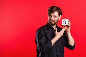 Man holding cube with number eight