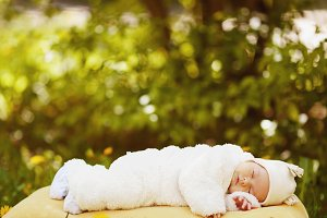 sleeping baby on big yellow pillow in flowers field