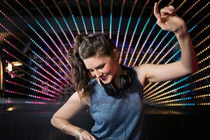 Pretty female DJ playing music