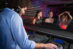 Male disc jockey playing music with three women dancing on the dance floor