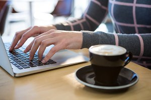 Woman using laptop with coffee on table