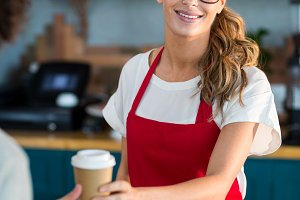 Smiling waitress serving a coffee to customer at counter in café